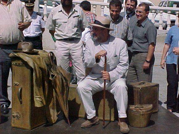"""Eduardo Úrculo sentado sobre su escultura """"Equipaje de ultramar"""". (Isla de Fuerteventura, 1995)"""